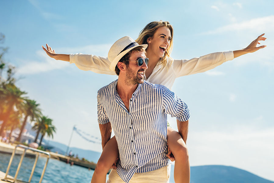 Personal Insurance - Man Carrying Wife with Her Arms Extended with Palm Trees in the Background